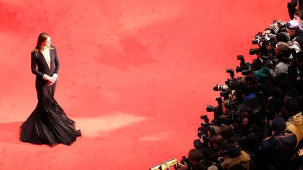 Frau posiert auf dem roten Teppich für Fotografen