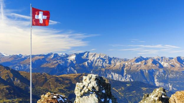 Schweizerische Berglandschaft mit Schweizer Flagge.