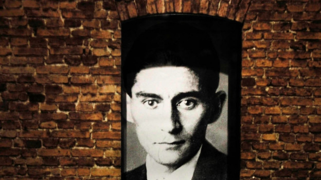 Ein Schwarz-Weiss-Foto von Kafka an einer Backsteinwand