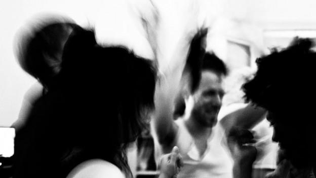 Schwarz-Weiss-Foto mit Menschen, die ein Fest feiern. Das Bild ist verschwommen.