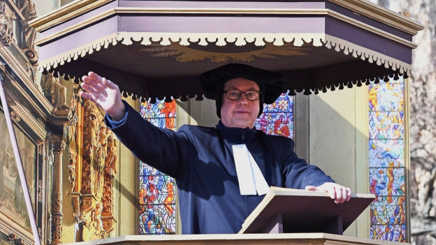 Ein als Luther verkleideter Mann steht auf einer Kanzler und hält eine Rede.