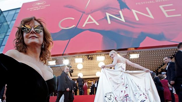 Der rote Teppich vor dem Kinoeingang. Eine Frau im weissen Kleid auf der Treppe, im Vordergrund eine Frau im schwarzen Kleid.