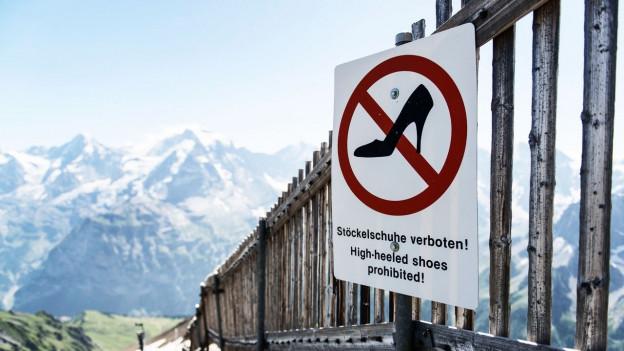 Ein Verbotsschild mit einem Stöckelschuh darauf, dahinter eine Bergkulisse.