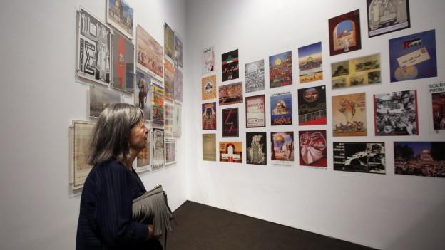 Eine Frau betrachtet die Bilder der Ausstellung «Jerusalem lebt»