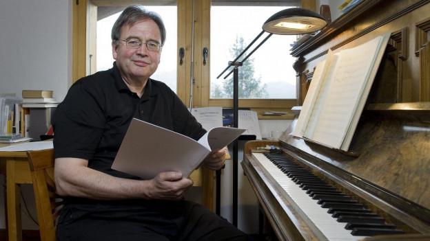 Ein Herr sitzt in einer Stube an einem Klavier