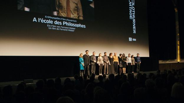 Menschen stehen vor Publikum auf einer erleuchteten Bühne