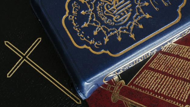 Abbild von einer Bibel und einem Koran.