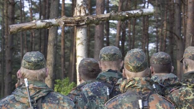 Rekruten der deutschen Bundeswehr vor einem Kruzifix aus Holz