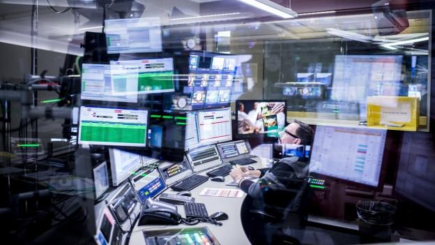 Ein Mann sitzt hinter dutzenden Bildschirmen und verfolgt das Geschehen