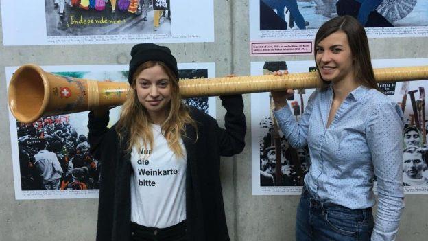 Lara Stoll und Lisa Stoll mit Alphorn vor Bilderwand
