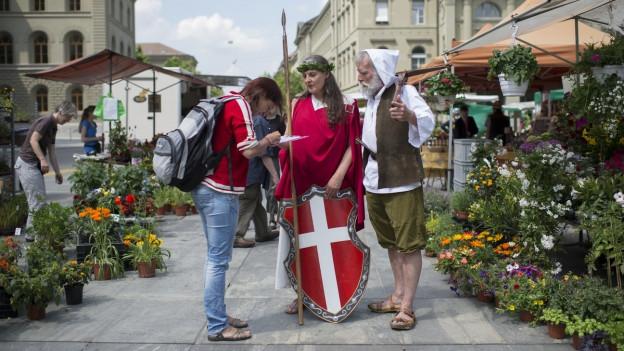 Eine Frau und ein Mann in Verkleidung sammeln Unterschriften für die Vollgeld-Initiative