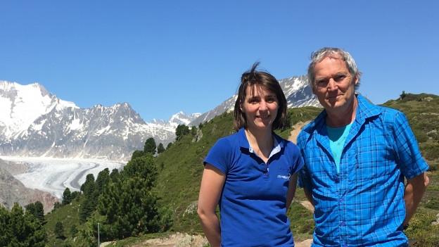 Eine Frau und ein Mann in Wanderkleidung auf einem Stein. Im Hintergrund der Aletschgletscher.