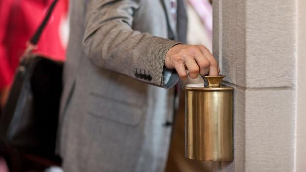 Mann spendet Geld in einer Kirche