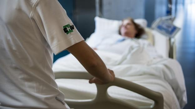 Eine Person, die im Spital arbeitet, schiebt ein Bett, auf welchem eine Patientin liegt, durch einen Spitalgang.