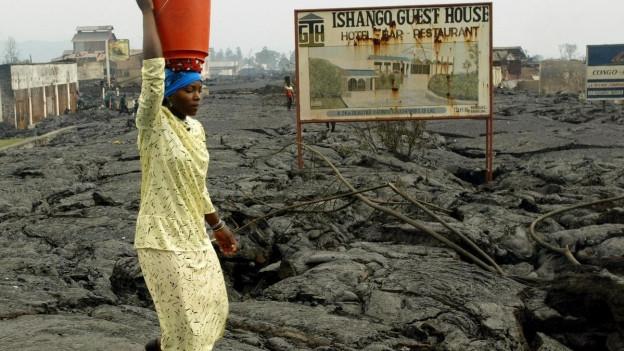 Eine Frau balanciert einen Eimer auf dem Kopf und geht durch Goma. Die Strassen wurden von Lava zerstört.