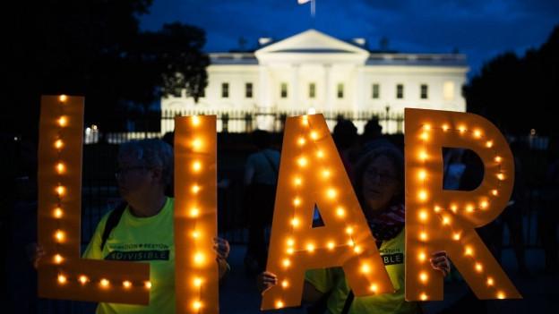 Zwei Frauen stehen vor dem Weissen Haus und halten Leuchtbuchstaben in die Luft, die das Wort «Liar» – Lügner – schreiben.