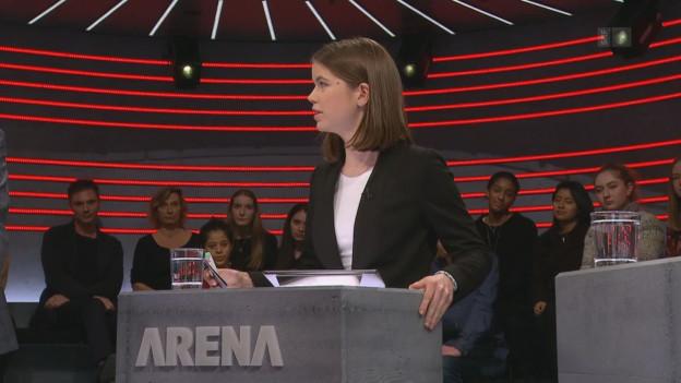 Eine junge Frau steht am Moderationspult von Arena.