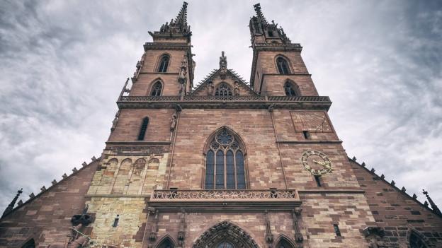 Das Basler Münster mit seiner roten Steinfassade, vor dem Hauptportal noch oben zu den Türmen geblickt.