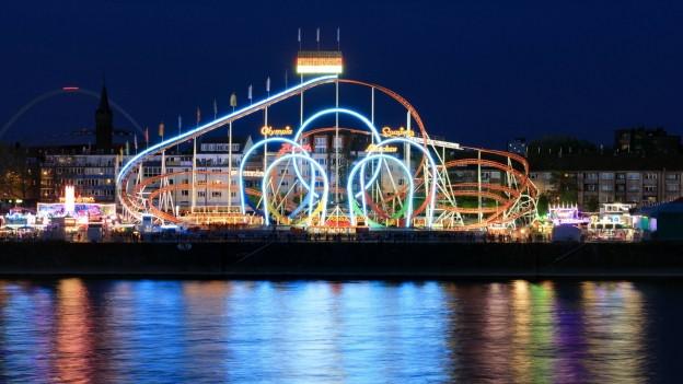 Nachtszene: Eine Achterbahn mit Windungen und Loopings ist belichtet vor dunklem Hintergrund