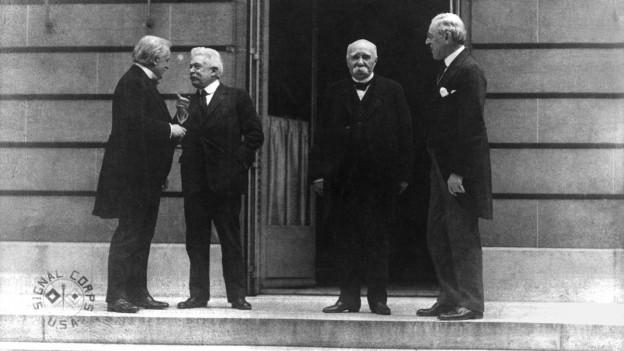 Historisches Schwarzweissfoto: Vier Männer stehen vor einem Gebäude