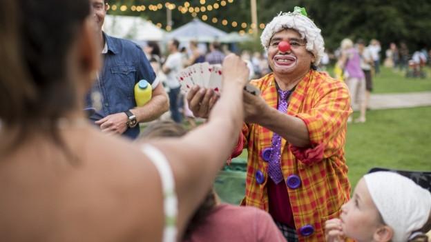 Ein als Clown verkleideter Mann hält Jasskarten in seiner Hand