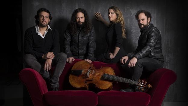 Vier Personen posieren vor einem Sofa und Streichinstrument