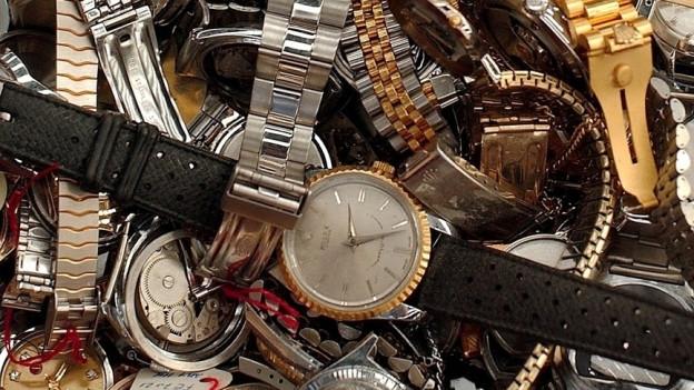 Verschiedenfarbige Uhren liegen lose übereinander