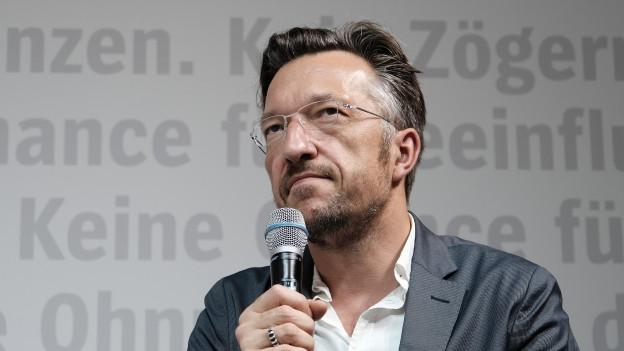 Ein Mann mit Brille hält ein Mikrofon in der Hand