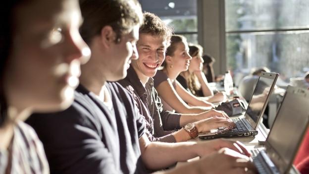 Junge Menschen sitzen nebeneinander in einem Vorlesungssaal