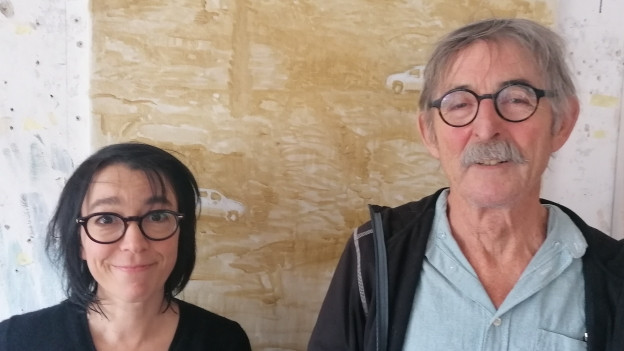 Eine Frau und ein Mann mit Brille blicken in die Kamera