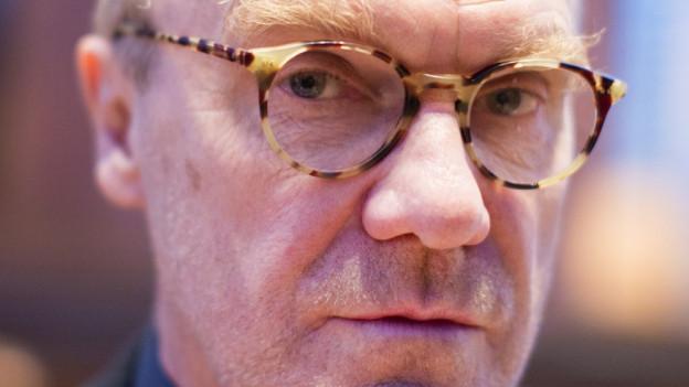 Ein älterer Mann mit Brille schaut in die Kamera