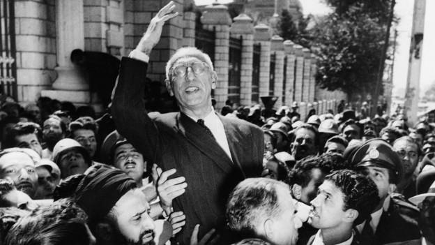 Ein älterer Mann mit Brille in einer Menschenmenge