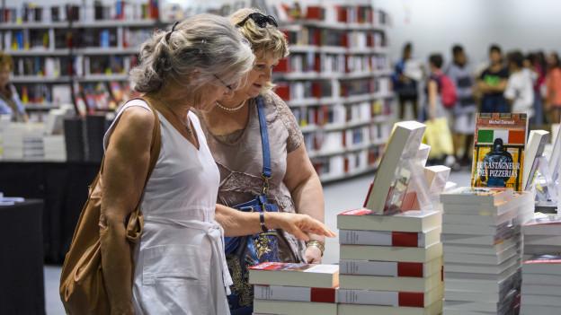 Zwei ältere Frauen stehen an einem Bücherstand in einem Buchladen