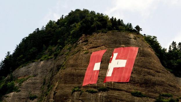 Eine in der Hälfte zerrissene, riesige Schweizer Flagge, die an einem Berg hängt
