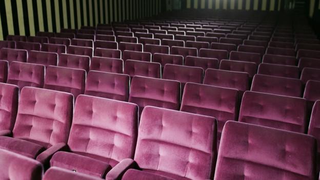 Blick in einen leeren Kinosaal mit violetten Sesseln