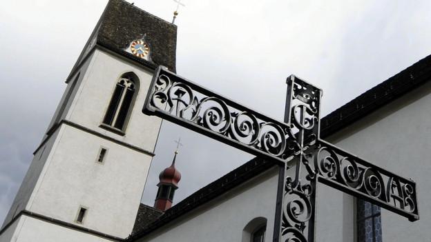 Blick auf eine Kirche in Schwyz mit einem Kreuz im Vordergrund