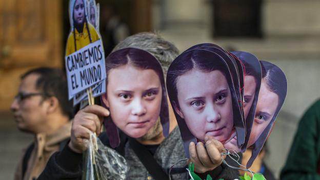 Mann mit mehreren Masken von Greta Thunberg vor seinem Gesicht