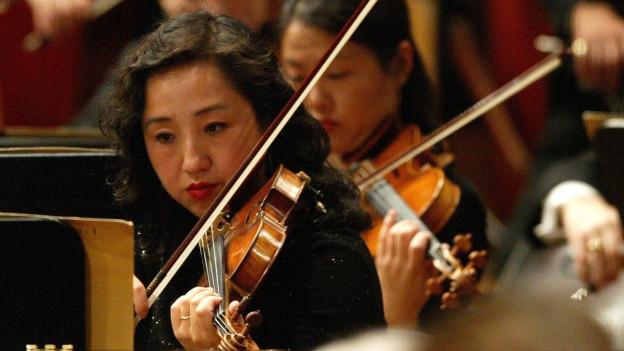 Frau mit schwarzen Haaren im Vordergrund mit einer Geige in der Hand, weiter hinten weitere Orchestermitglieder