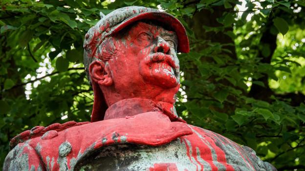 Denkmal aus Bronze von einem Herren mit roter Farbe bespritzt
