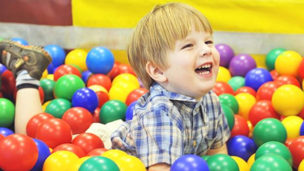 Ein Kind mit farbigen Bällen.