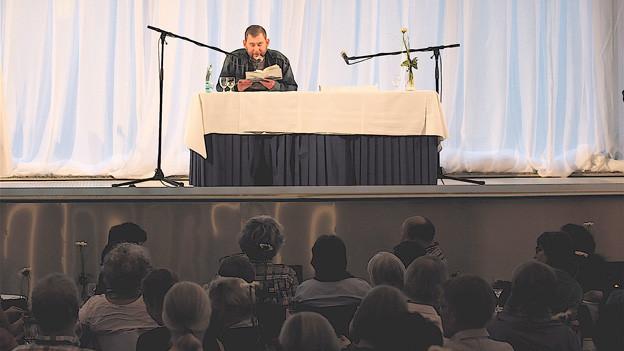 Oleg Jurjew liest im Bad des Rehazentrums Leukerbad. Das Publikum sitzt im leeren Thermalbecken.