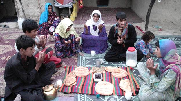 Eine afghanische Familie betet vor dem Fastenbrechen.