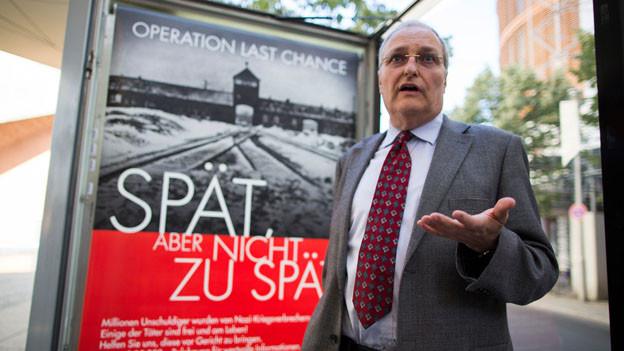 Der Direktor Simon Wiesenthal Centers Efraim Zuroff vor dem umtrittenen Plakat.