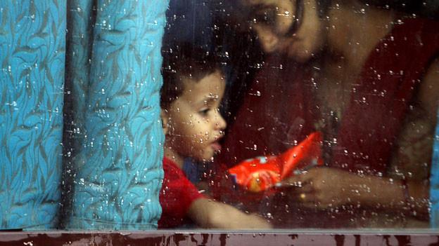 Ein Kind mit seiner Mutter in einem Zug in Delhi.