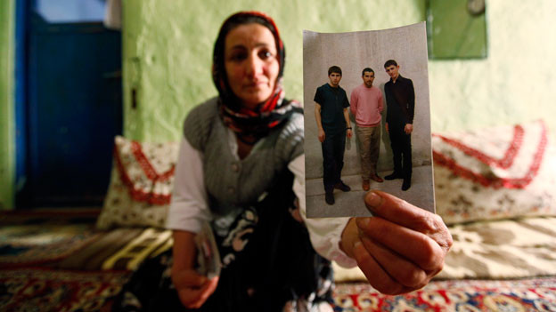 Verfolgt und eingesperrt: Eine kurdische Frau in der Türkei zeigt ein Foto ihres inhaftierten Sohnes.
