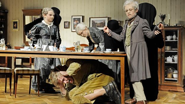 Szenenbild: Ein Esstisch, drei als alte Menschen verkleidete Kinder, unter dem Tisch kauert ein erwachsener Mann.
