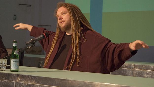 Der Internetpionier weitet seine Arme aus bei einer Rede.