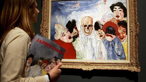 Eine Frau steht vor einem Bild von James Ensor bei einer Austellung.