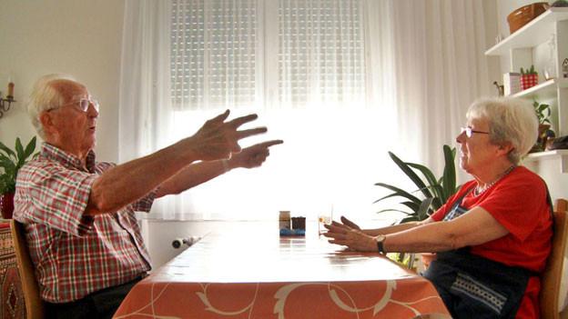 Vater und Mutter sitzen sich gegenüber am Tisch. Der Vater gestikuliert mit den Armen.