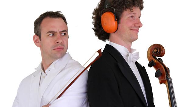 Zwei Männer mit Cello, Bogen und Gehörschutz.